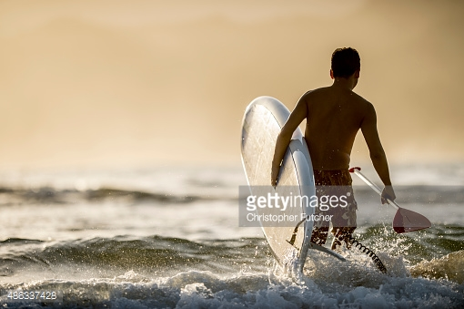 486337428-man-going-into-the-surf-gettyimages